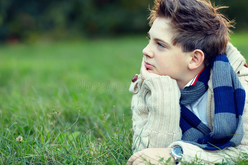 Handsome teenager boy lies on grass and thinks royalty free stock photography
