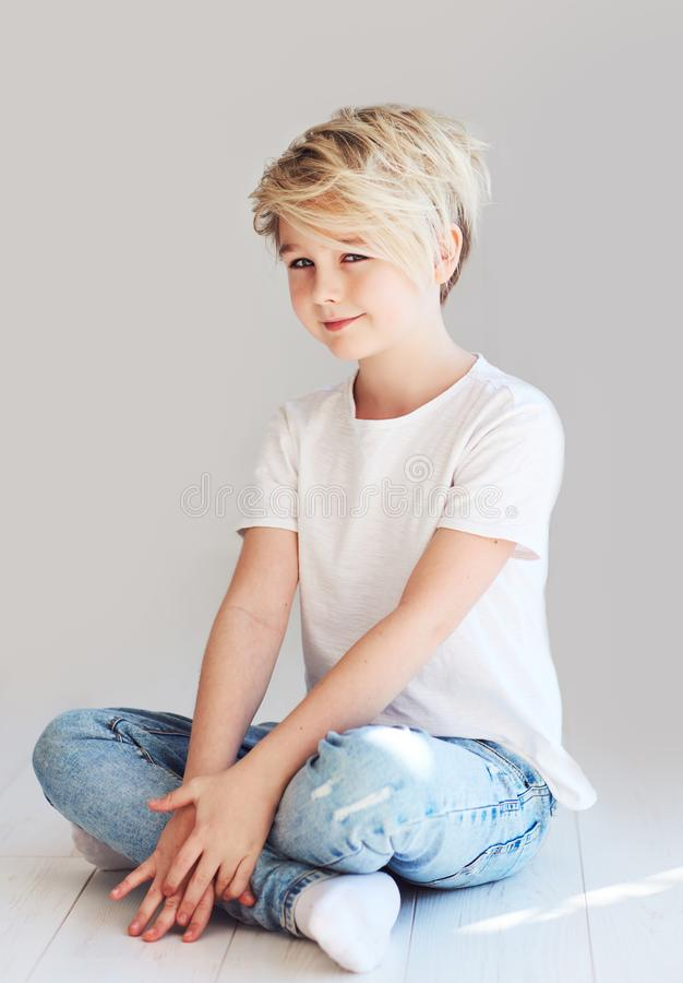 Handsome teenager boy sitting on the floor stock photos