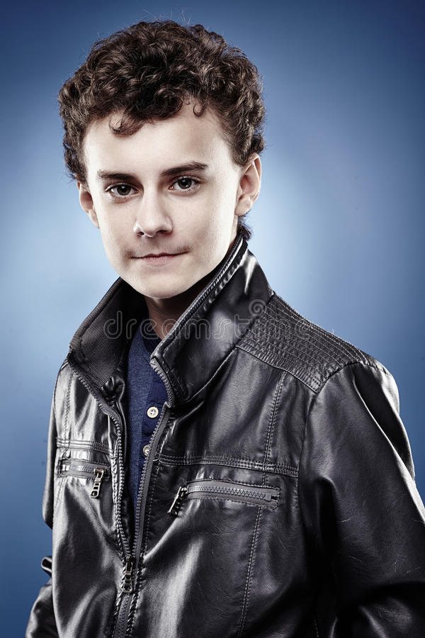 Handsome teenager with curly hair wearing black leather jacket royalty free stock photography