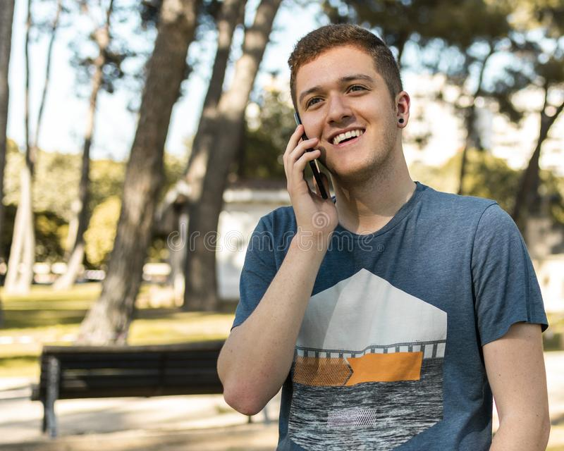 Handsome teenager talking on a mobile phone outdoors. Picture of a handsome teenager talking on a mobile phone in a park royalty free stock photography