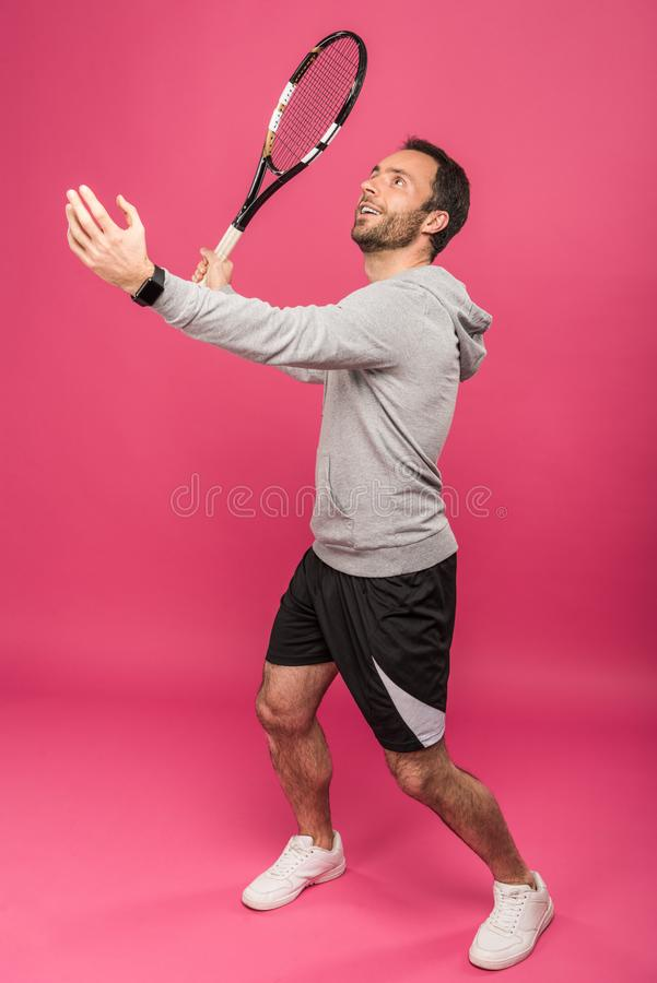 Handsome tennis player with racket, isolated. On pink stock photos