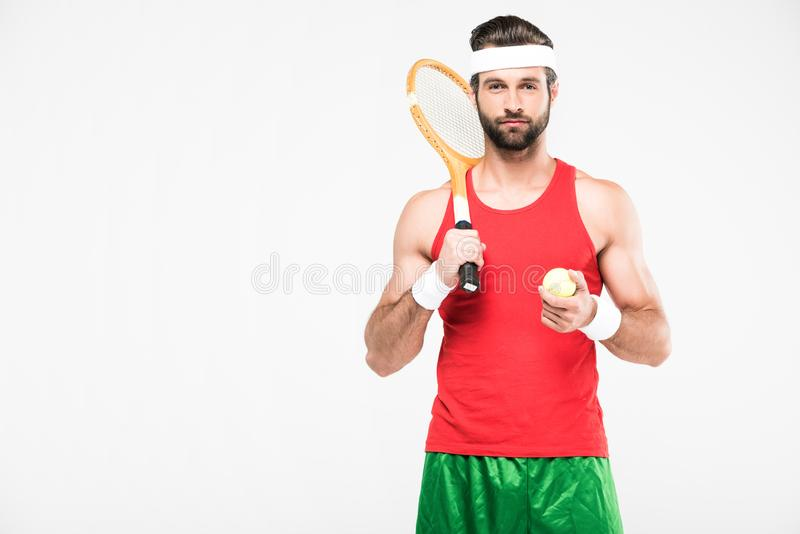 Handsome tennis player with retro wooden racket and ball. Isolated on white stock image