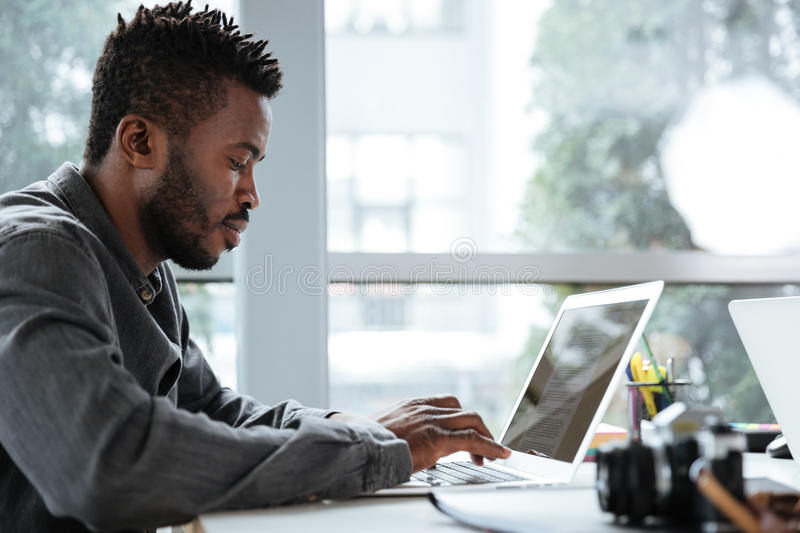 Handsome thinking serious young man sitting in office coworking royalty free stock image