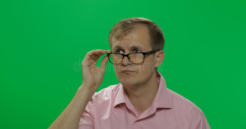Handsome thoughtful man in pink shirt thinks about something. Chroma key royalty free stock image