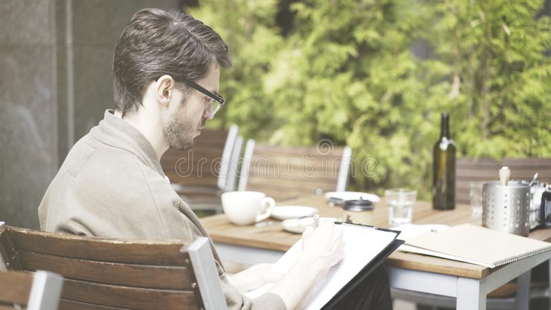 A handsome european man in eyeglasses making notes drawing at cafe outdoors royalty free stock photography
