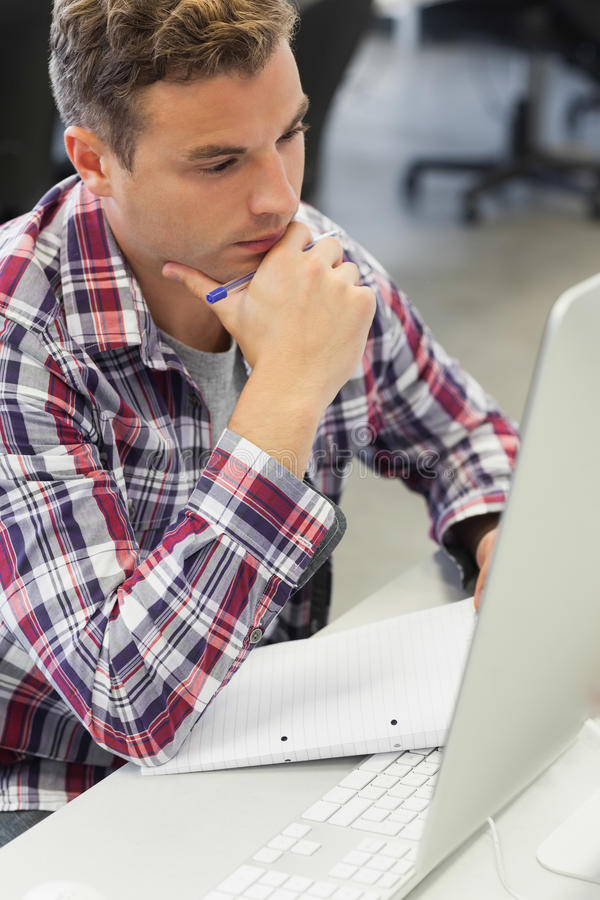 Handsome thoughtful student using computer taking notes stock images