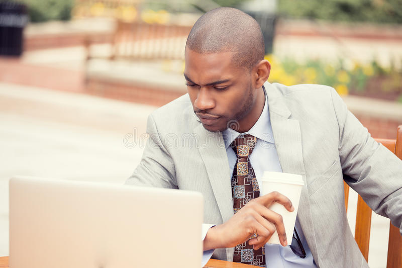 Handsome thoughtful young business man working on laptop outdoors. Outside corporate office building. Instagram filter effect stock images