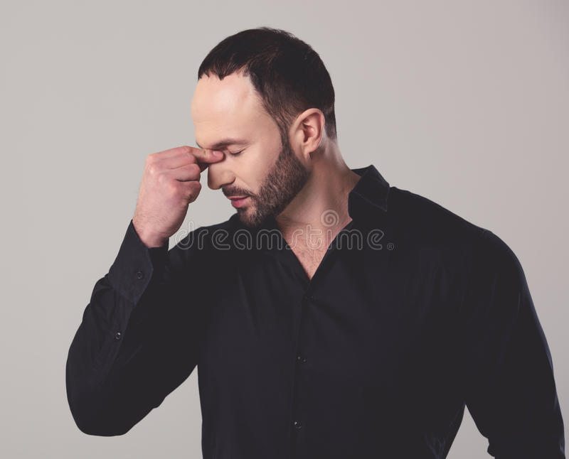 Handsome tired businessman. In black shirt is massaging his nose bridge, on gray background royalty free stock images