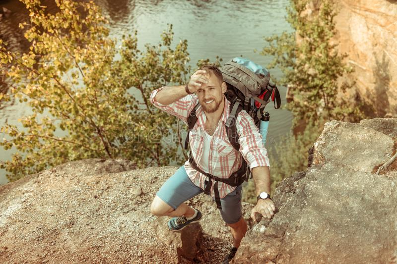 Handsome tired man climbing the hill alone royalty free stock image
