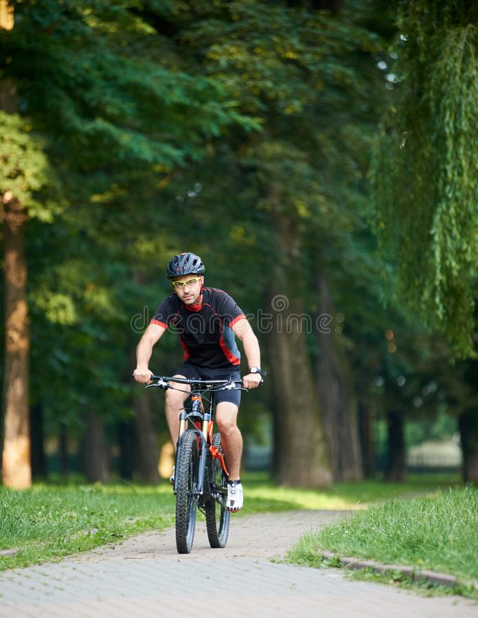 Male cyclist training in green park royalty free stock photography