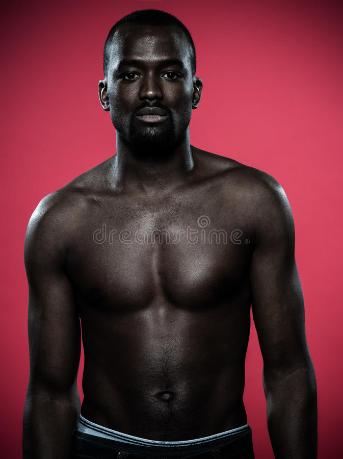 Handsome topless young african man. One young handsome african man topless portrait in studio on red background stock image