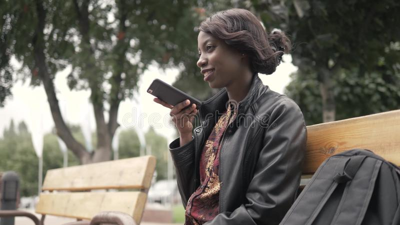 Handsome trendy african american black woman recording voice message on cell phone that he is holding, outdoor in city royalty free stock photography