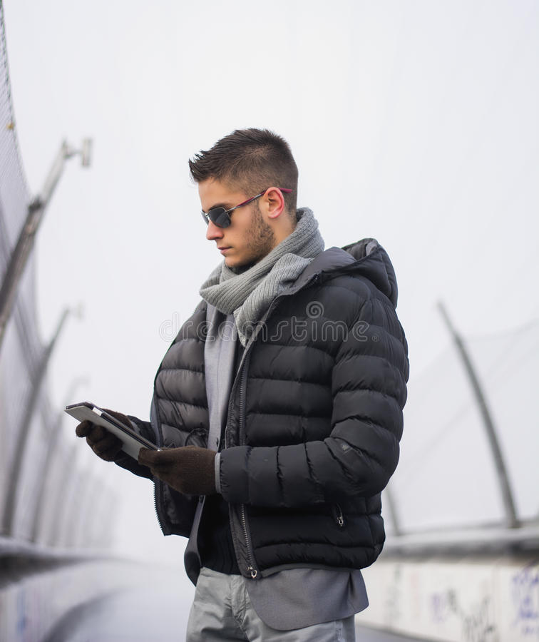 Handsome trendy man in winter fashion looking royalty free stock photography