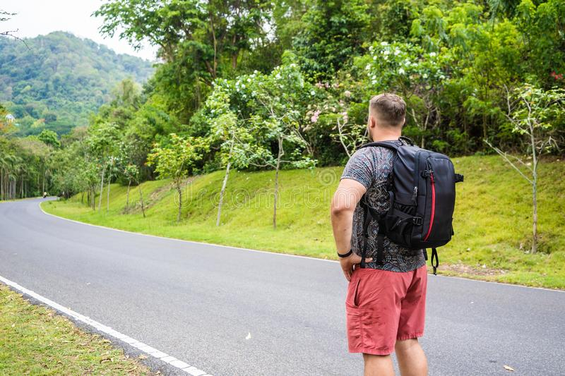 Handsome tropical forest with a traveler young man with a backpack on the road to Thailand forest. A man walks on a royalty free stock image
