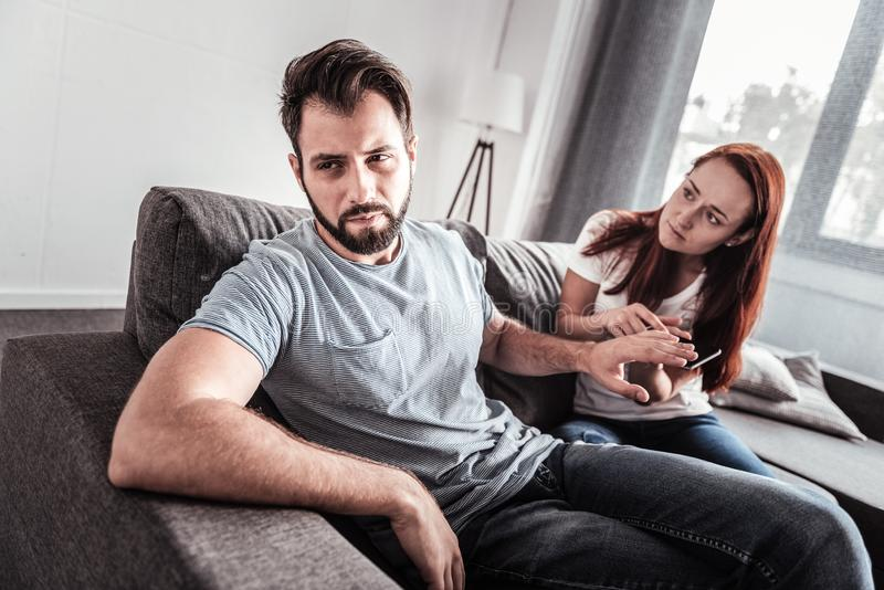 Handsome unhappy man turning away from his wife stock photos
