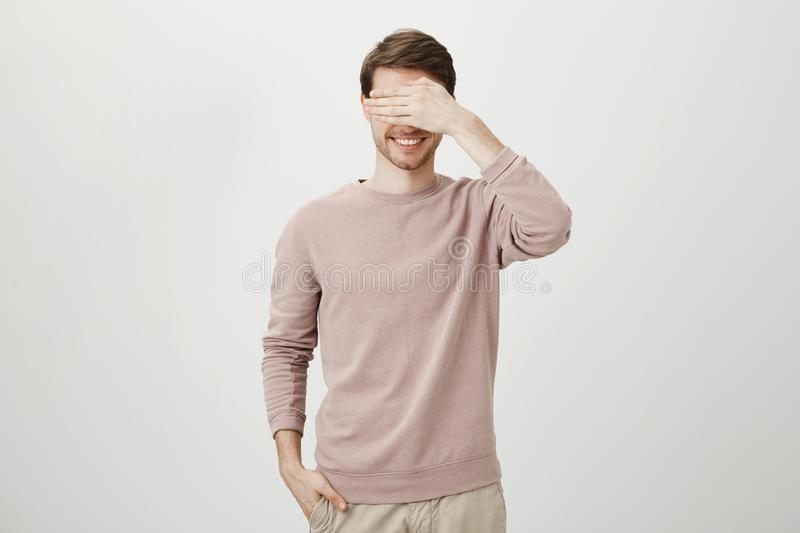 Handsome unshaved caucasian adult man holding hand in pocket while covering eyes with another and smiling cheerfully royalty free stock image
