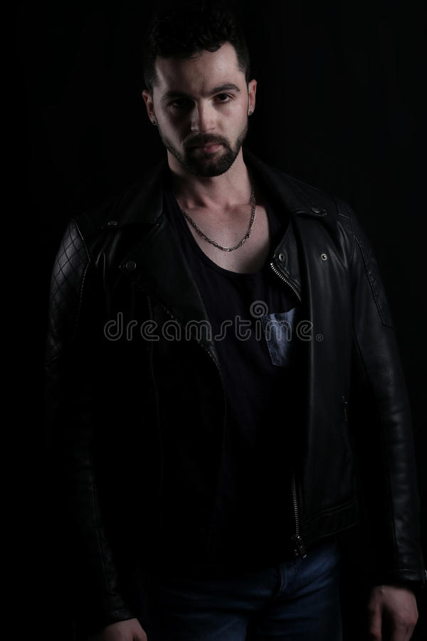 Handsome vampire wearing a black leather jacket royalty free stock photography