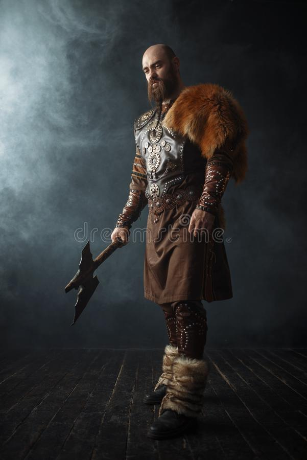 Handsome viking with axe, nordic barbarian image. Handsome viking with axe dressed in traditional clothes, nordic barbarian image. Ancient warrior in smoke on stock photo