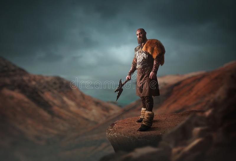 Handsome viking with axe on the top of mountain. Handsome viking with axe dressed in traditional nordic clothes standing on the top of rocky mountain royalty free stock images