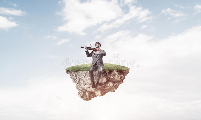 Handsome violinist on floating island in blue sky play his melody royalty free stock photography