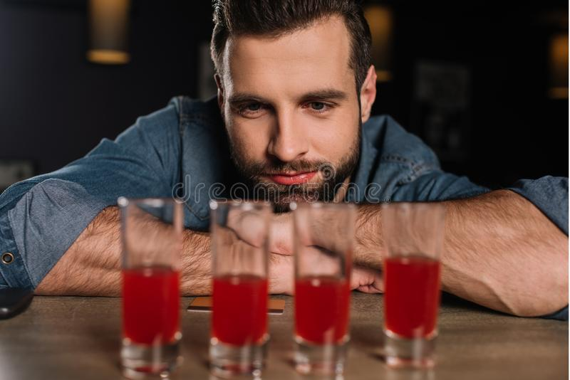 handsome visitor sitting at bar counter and looking at four royalty free stock image