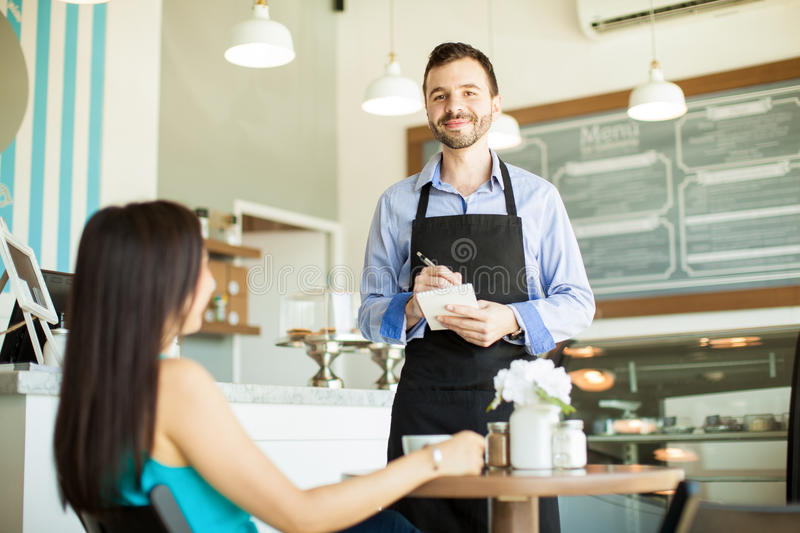Handsome waiter doing his job royalty free stock photos