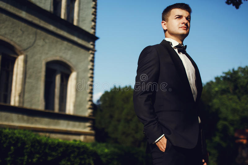 Handsome wealthy confident groom near old mansion background stock images