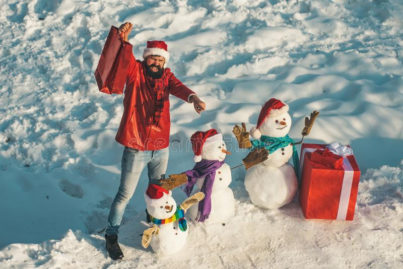 Handsome Winter Man with gift and snowman in frosty winter Park. Funny Santa man posing with red gift box on winter stock images