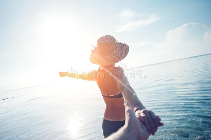 Handsome woman in hat guiding a man by the hand into the ocean stock image