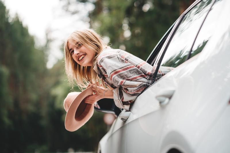 Handsome woman sitting in car looking from window on beautiful view in forest. Boho woman sitting in car looking from window on be stock photos