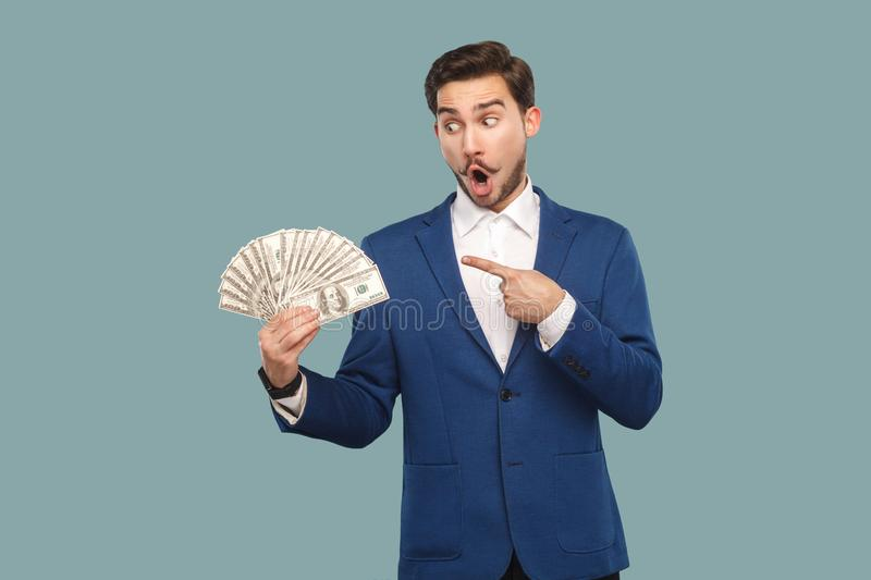 Handsome wondered businessman in blue jacket standing and holding many dollars in hand, pointing and looking at money with amazed stock photos