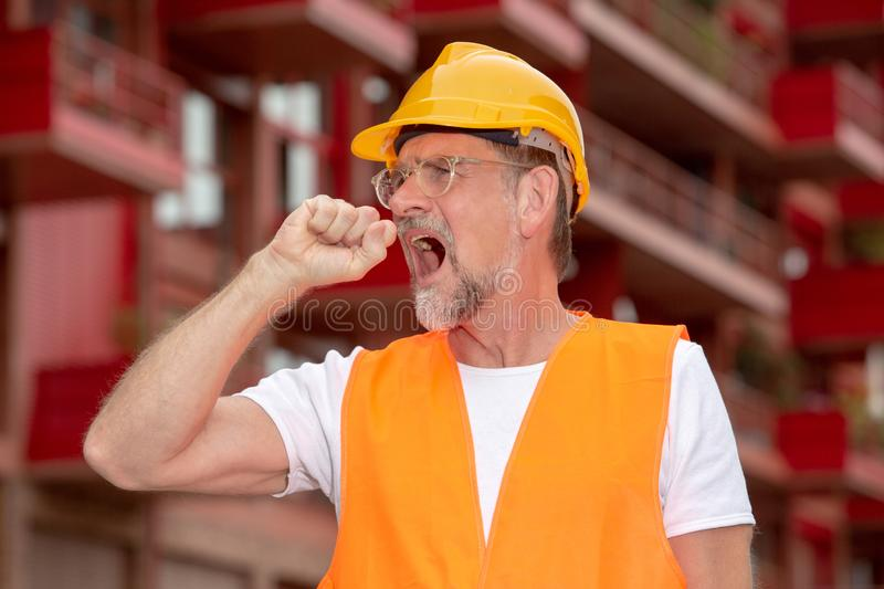 Handsome worker in his 50s with helmet looking tired royalty free stock images