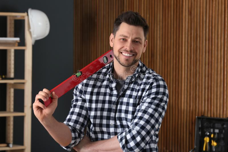 Handsome working man with building level. Home repair stock photo