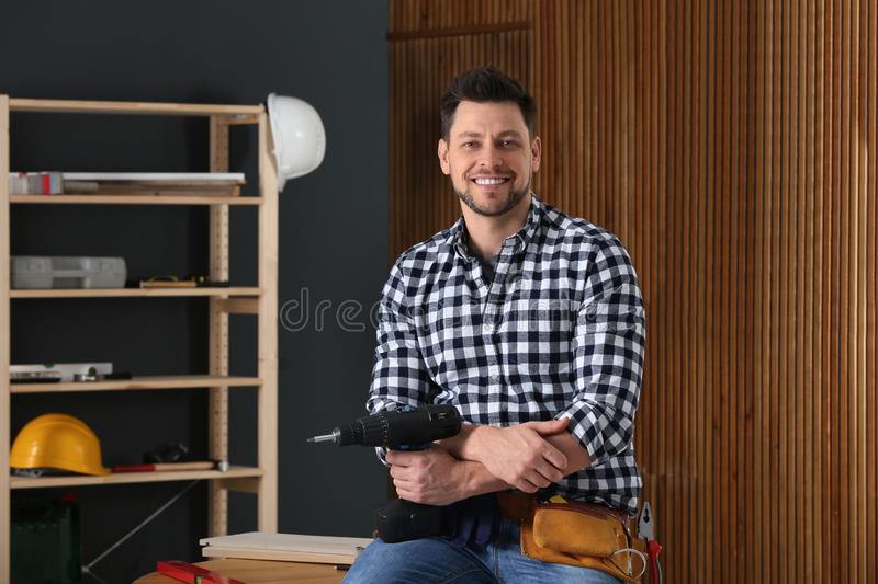 Handsome working man with electric screwdriver indoors royalty free stock photos
