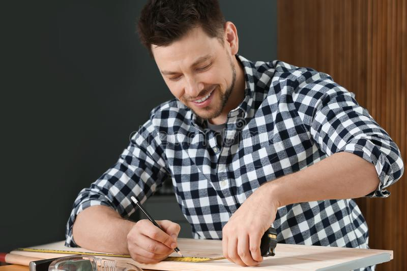 Handsome working man making marks on timber at table. Home repair stock photography