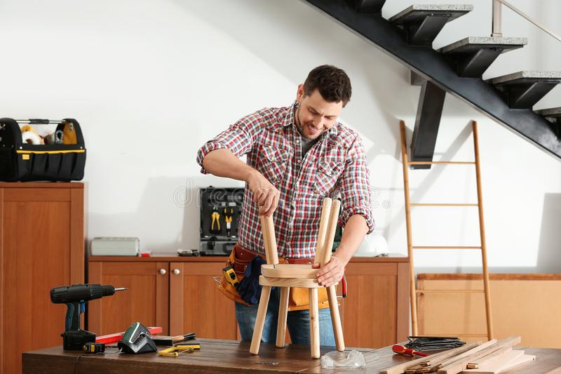 Handsome working man repairing wooden stool royalty free stock photography