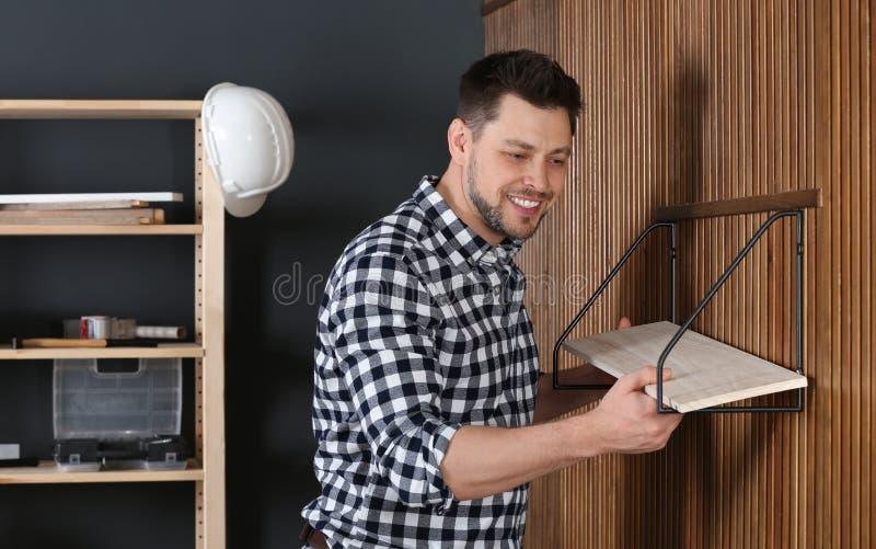 Handsome working man setting shelf indoors stock photography