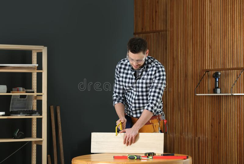 Handsome working man using hand saw. Home repair royalty free stock photography