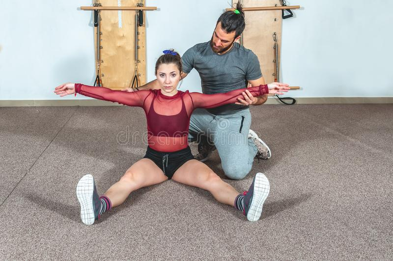 Handsome yoga male personal trainer with a beard helping young fitness girl to stretch her muscles after hard training workout, re royalty free stock photo