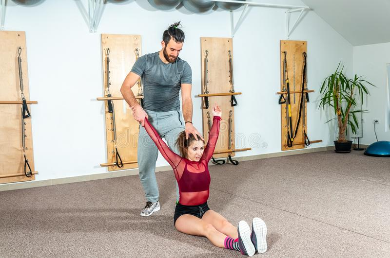 Handsome yoga male personal trainer with a beard helping young fitness girl to stretch her muscles after hard training workout, re stock photography