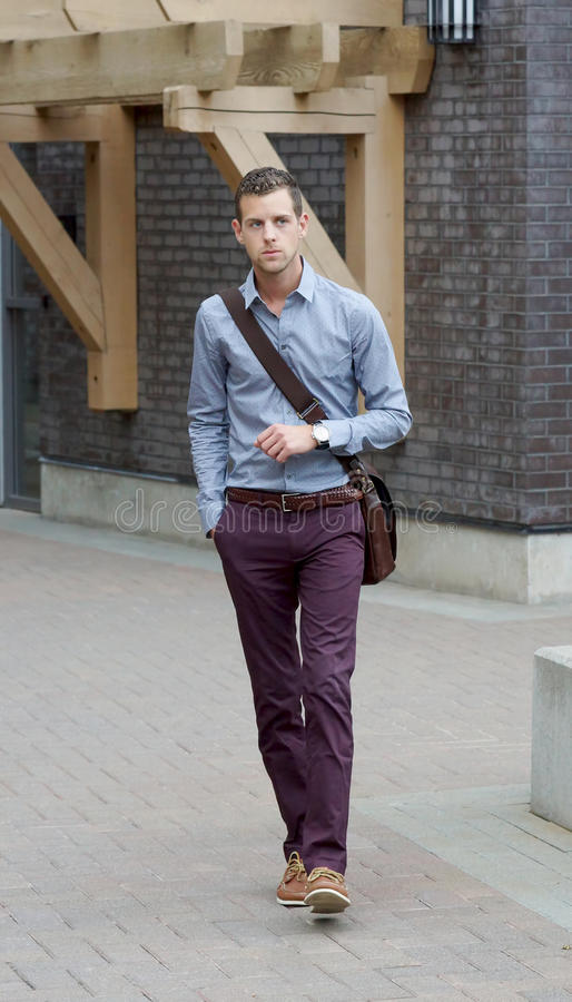 Handsome Young Adult Male Walking With A Messenger Bag. Young adult male walking in an urban area carrying a messenger bag royalty free stock image