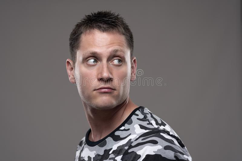 Handsome young adult man in army shirt looking back over the shoulder at copy space stock photography