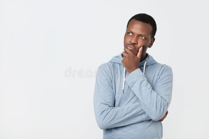 Handsome young African American man looking up with thoughtful and skeptical expression stock photography