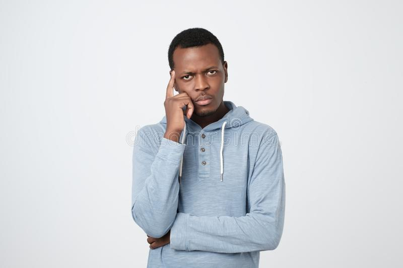 Handsome young african american man looking up with thoughtful and skeptical expression royalty free stock image