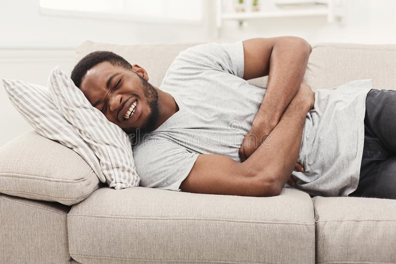 Handsome young african-american man suffering from stomachache stock photography