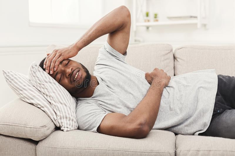 Handsome young african-american man suffering from stomachache and headache royalty free stock image