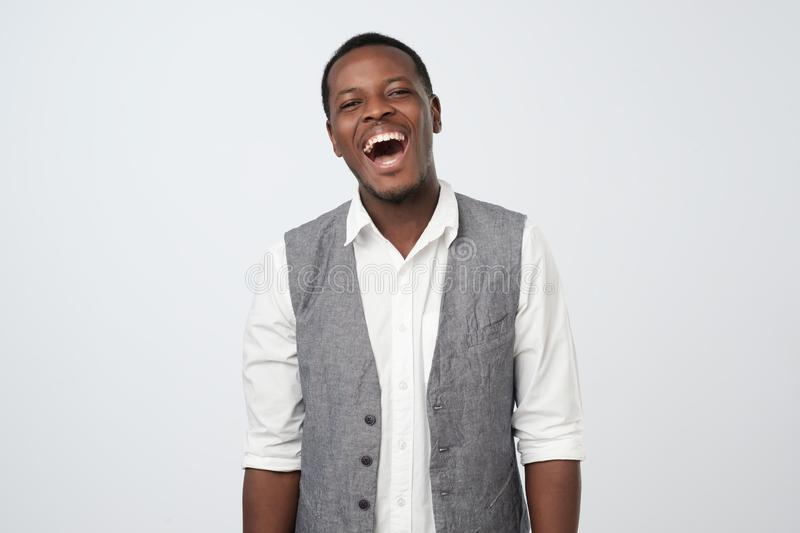 Handsome young african male laughing out loud at funny joke at work stock photography