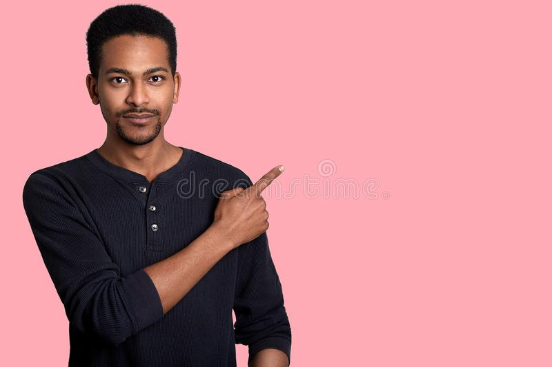 Handsome young african man dresses black shirt, points aside with his right hand. Good looking male shows somethig interesting to. His friends. Model poses in royalty free stock photography