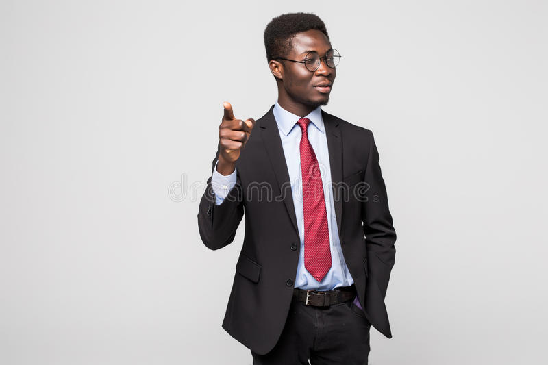 Handsome young African man in formalwear pointing on you while standing against grey background. Handsome African man in formalwear pointing on you while stock photo