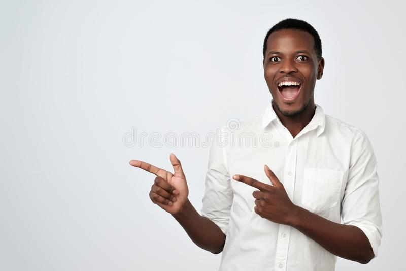 Handsome young african man pointing away and looking at camera with smile royalty free stock photography